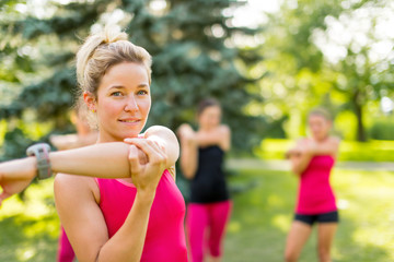 Cheerful young woman streching her arm before jogging