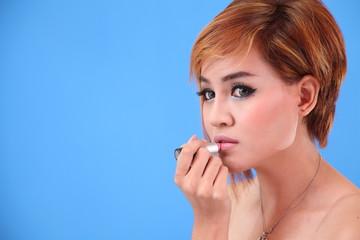 Portrait of Asian lady applying lipstick
