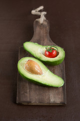 avocado with tomatoes on a wooden Board