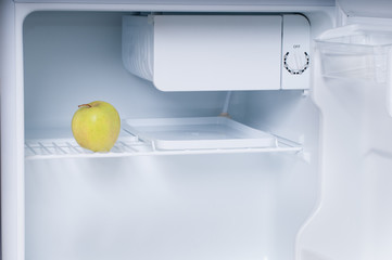 One apple in open empty refrigerator