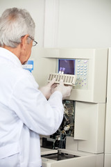 Scientist Loading Analyzer With Samples