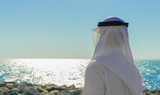 Man in Arab dress looks at the sea