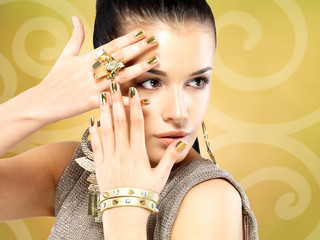 Pretty woman with golden nails and beautiful gold ring