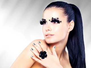 woman with long black false eyelashes makeup and golden nails