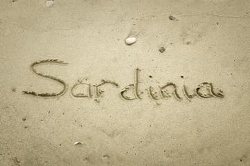 Sardinia - written in sand on beach texture
