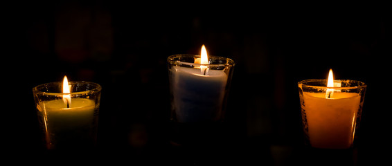 Burning candle on black background.