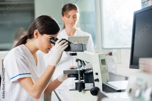 Female Researcher Looking Through Microscope