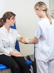 Nurse Drawing Blood From Businesswoman's Arm