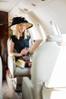 Woman With Digital Tablet And Drink Glass In Private Jet