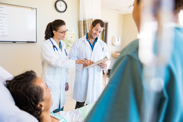 Doctors Discussing Notes With Patient And Nurse In Foreground