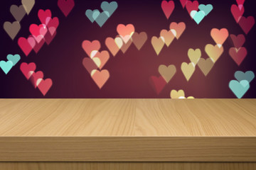 Holiday background with empty wooden table and heart bokeh light