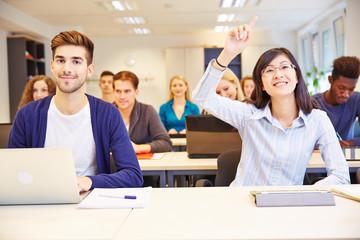 Schülerin hebt Hand im Unterricht