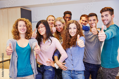 Jugendliche Gruppe hält Daumen hoch - 60390622