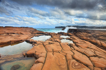 Waves splash on magnificent eroded rock formations