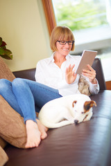 Relaxed women with pad and dog on leather sofa