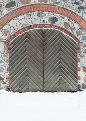 Old wooden gate with pig-iron rivets in a granite wall in the wi