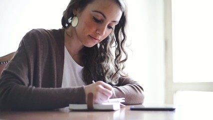 beautiful woman working at home on the table using smarphone