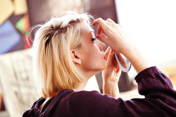 woman applying false lashes