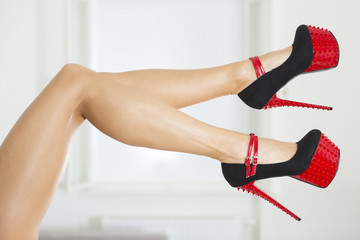 Legs of a woman in extreme high heels with spikes