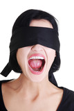 Portrait of young blindfold woman screaming