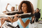 Pretty ethnic girl exercising on weight machine