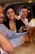 Young woman drinking beer in pub