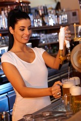 Female bartender tapping beer in bar