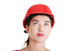 Confident female worker in helmet looking up.