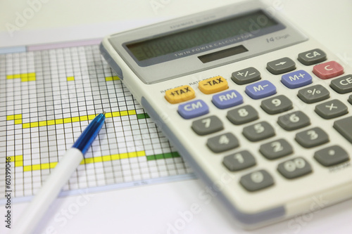 pen and calculator for financial calculating on the office table