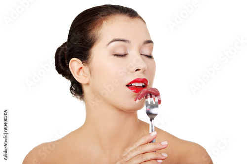 Young beautiful woman eating raw meat.