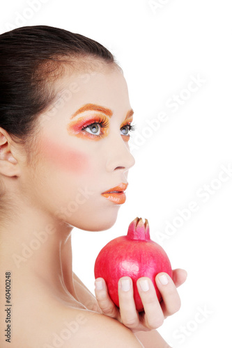Portrait of young beautiful woman with pomegranate