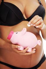 Young beautiful pregnant woman holding a pink piggybank