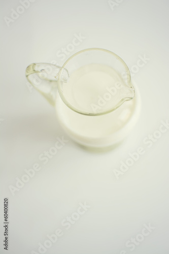 Glass jar of milk on a white surface