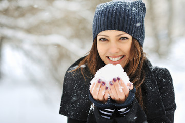 Beautiful woman playing with snow in park