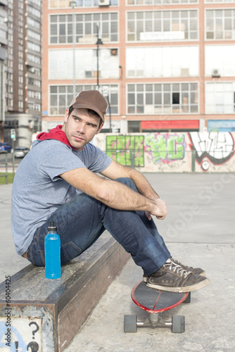 Skateboarder sitting in the park with skate and bottle of energy