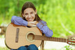 smiling teenage girl playing guitar