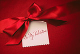 Red bow and white card for gift on velvet  background
