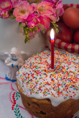 Easter cake with a lit candle, flowers, eggs and angel figurine