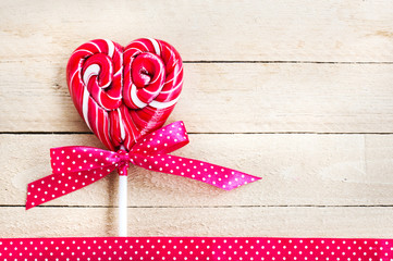 Red heart-shaped lollipop of valentines day on texture backgroun