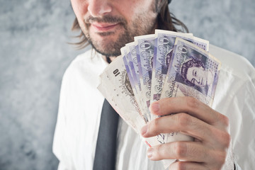 Businessman holding British pounds money