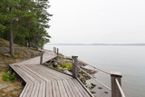 Rocky lakeshore with wooden pathway poster