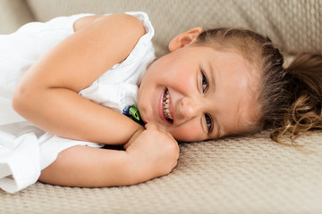 Portrait of a laughing little girl lying down