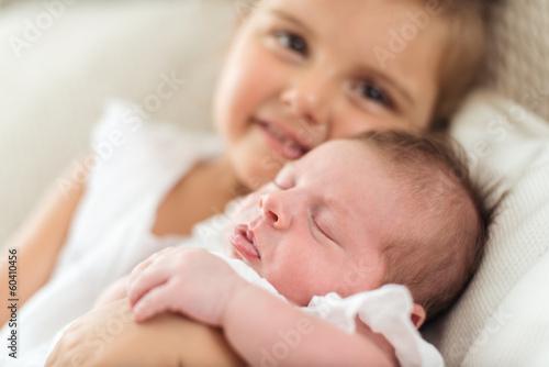 Newborn  in a christening dress in her sister