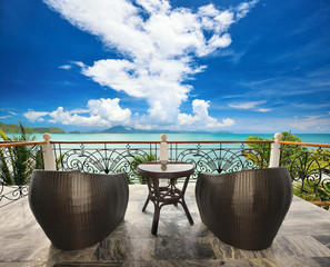 Terrace lounge with rattan armchairs and seaview.