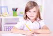 Little girl sitting at desk in room