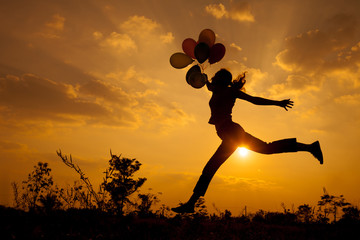 woman with balloons jumping on the nature of the evening