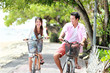Young couple riding bicycle together