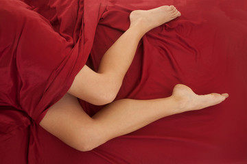Woman legs red sheet top view barefoot