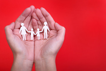 Paper Family in Hands over red background. Family and Kids