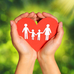 Paper Family and Heart in Hands over Green Background